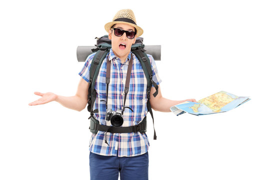 Lost male tourist holding a map and gesturing with hands