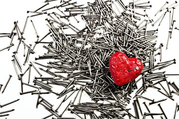 Red heart on pile of iron nails, pierced by a nail