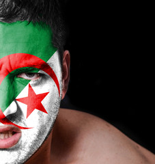 Portrait of angry man with painted flag of Algeria