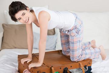 lächelnde frau kniet auf ihrem koffer