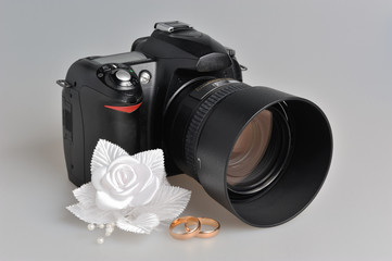 Photo camera, wedding boutonniere, rings on gray