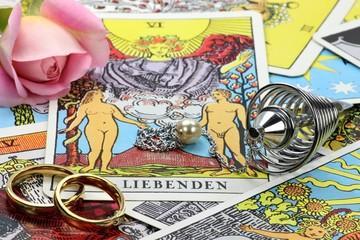 Tarotkarte 'Die Liebenden' mit Spiralpendel und Trauringen