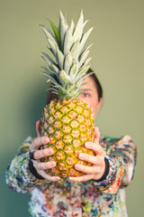 Fashion girl holding pineapple in front of face