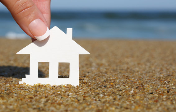 Paper house on the beach. Concept of mortgage. Macro