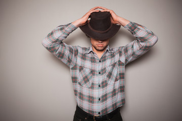 Young cowboy in plaid shirt against a green wall