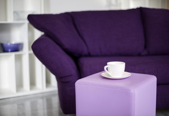 cup and purple couch
