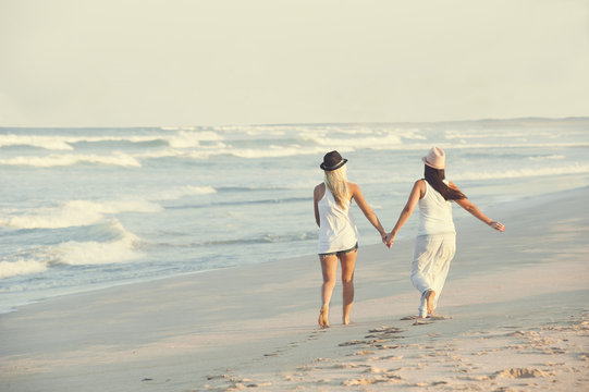 two attractive lesbian girls walking on the beach holding hands