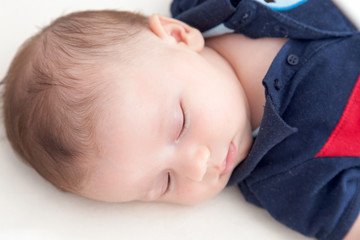 Close-up of a baby boy sleeping on the bed