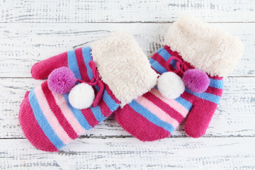 Striped mittens on wooden background