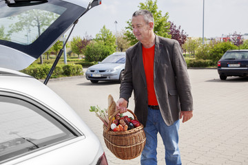 Man lifts filled basket in the car