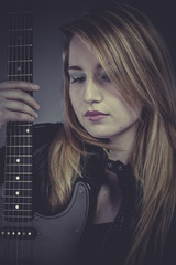 Heavy, Beautiful blond girl with black electric guitar