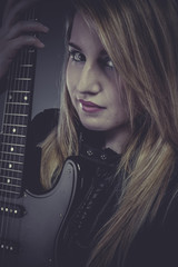 Beautiful blond girl with black electric guitar