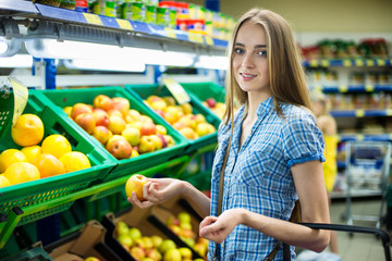 woman choosing fruits during shopping at supermarket