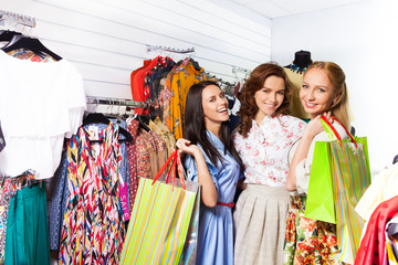 Three happy women with bags in shop