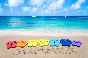 "Sign ""Summer"" and color flip flops on sandy beach"