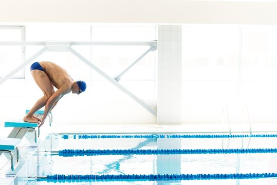 Young muscular swimmer in low position on starting block