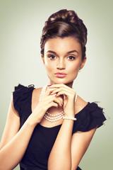 portrait of beautiful brunette woman wearing pearl  jewelry. loo