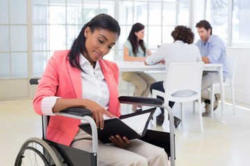 Woman in wheelchair reading document with colleauges in backgrou