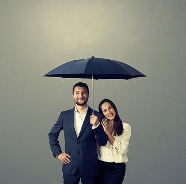 smiley couple under umbrella