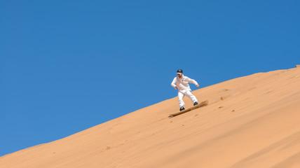 Man sandboarding in Namibia