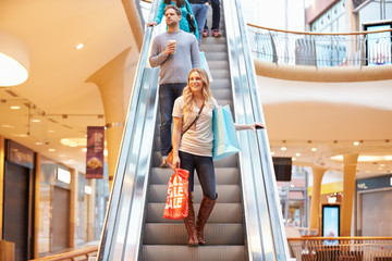 Female Shopper On Escalator In Shopping Mall