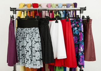 Wardrobe with colorful summer skirts displayed on a rack.