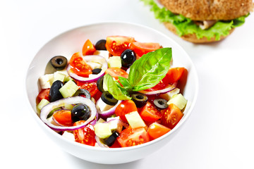 Light greek salad with fresh vegetables and burger in the backgr