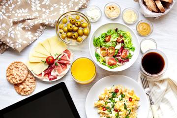 Fresh continental breakfast. Healthy food. Tablet, black screen.