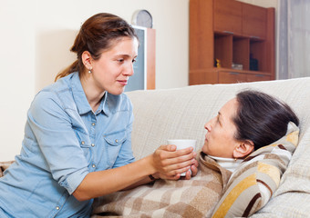 Adult daughter caring for sick mature mother