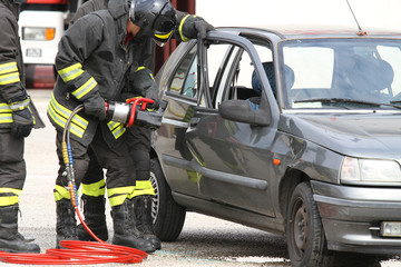 firefighters with shears open the car doors after a serious car