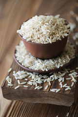 Close-up of ceramic tableware with raw brown rice, vertical shot