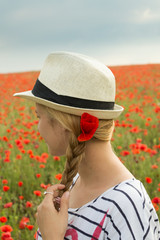 Girl in hat stands in poppy field