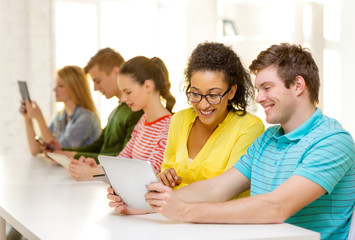 smiling students looking at tablet pc at school