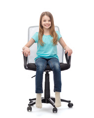smiling little girl sitting in big office chair