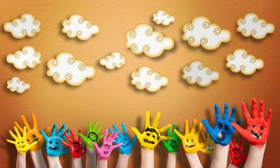 angemalte Kinderhände vor Wolkenhintergrund
