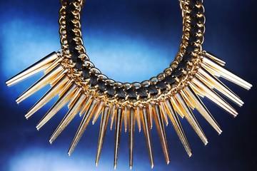 Shiny gold necklace on the blue background.