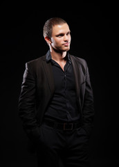 Strong and handsome man in suit over dark background