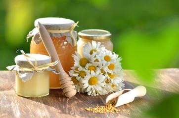 Obraz słoiki pełne świeżego miodu i kwiaty w pasiece  - fototapety do salonu