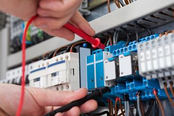 Electrician Examining Fusebox With Multimeter Probe