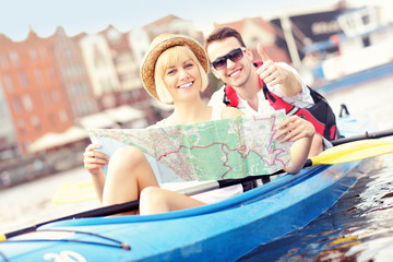 Young tourists with a map in a canoe