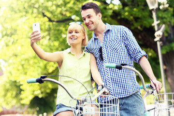 Happy couple taking pictures of themselves on a bike