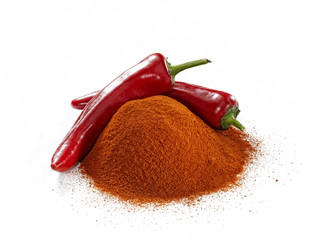 Minced and whole red peppers on white background