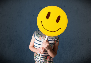Wall Mural - Young woman holding a smiley face emoticon
