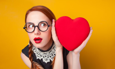 Nerd redhead girl with heart shape on yellow backgorund.