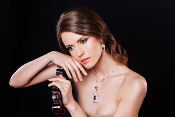 beautiful brunette woman with luxury accessories. on black