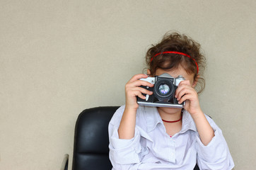 cute kid photographer holding vintage camera during playing acti