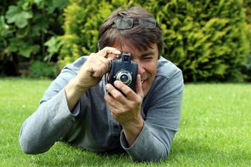 Fotograf liegt auf Rasen hat alte Boxkamera