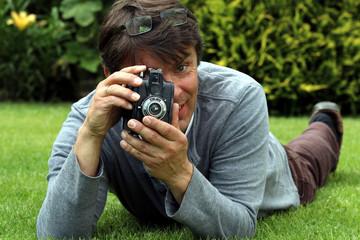 Alter Fotoapparat, Mann auf Wiese macht Foto