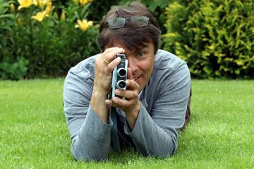 Mann auf Wiese filmt direkt in die Kamera