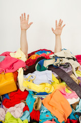 Man hands reaching out for help from a big pile of woman clothes